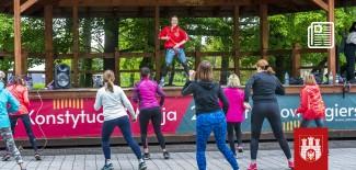 zajęcia w parku - na scenie instruktorka zumby, obok sceny ćwiczące osoby